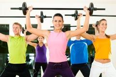 Grupo de la aptitud con el barbell en gimnasia Fotografía de archivo