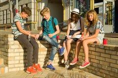 Grupo de la comunicación y de la reconstrucción de 4 adolescentes de los niños Los amigos juegan a un juego de mesa, lanzando dad imagen de archivo