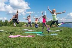 Grupo de la diversión de mujer joven del ajuste que salta al aire libre día soleado Foto de archivo libre de regalías