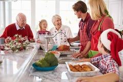 Grupo de la familia extensa que prepara la comida de la Navidad en cocina Foto de archivo libre de regalías