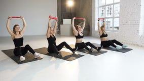 Grupo de la hembra feliz cuatro en trajes de los deportes del cuerpo que ejercita con las bandas de la resistencia en el piso en  almacen de video