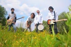 Grupo de la música de cuatro en parque Foto de archivo libre de regalías
