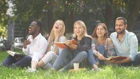 Grupo de la raza mixta de estudiantes que se sientan junto en el césped verde del campus universitario almacen de metraje de vídeo