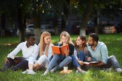 Grupo de la raza mixta de estudiantes que se sientan junto en el césped verde del campus universitario imagenes de archivo