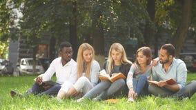 Grupo de la raza mixta de estudiantes que se sientan junto en el césped verde del campus universitario almacen de video