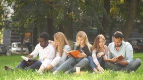 Grupo de la raza mixta de estudiantes que se sientan junto en el césped verde del campus universitario metrajes