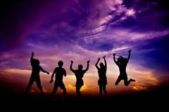 Grupo de la silueta de amigos que tienen saltos de la diversión Imagen de archivo
