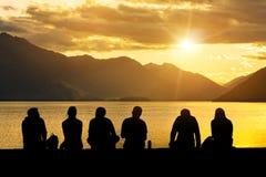 Grupo de la silueta de gente joven que se sienta en la playa Imagen de archivo libre de regalías