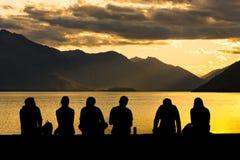 Grupo de la silueta de gente joven que se sienta en la playa foto de archivo libre de regalías