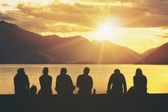 Grupo de la silueta de gente joven que se sienta en la playa fotografía de archivo libre de regalías