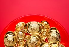 Grupo de la visión superior de lingotes de oro en la bandeja roja en el fondo rojo CH Fotos de archivo
