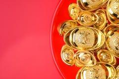 Grupo de la visión superior de lingotes de oro en la bandeja roja en el fondo rojo CH Imagen de archivo