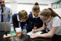 Grupo de laboratório do laboratório dos estudantes na sala de aula da ciência fotografia de stock royalty free