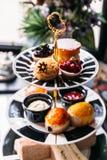 Grupo de lanche inglês que inclui o chá quente, a pastelaria, os bolos, os sanduíches e mini tortas na tabela superior de mármore foto de stock