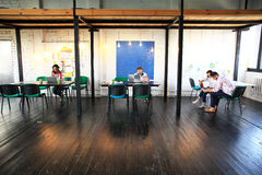 Grupo de lanzamiento joven que trabaja en oficina moderna Espacio abierto, ordenadores portátiles y papeleo imagen de archivo