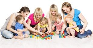 Grupo de las madres y de los niños que juega los juguetes, juego de la madre con el bebé Imágenes de archivo libres de regalías