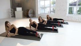 Grupo de las mujeres jovenes de los pilates de los aeróbicos con las gomas en fila en el piso en la clase de la aptitud Forma de  almacen de metraje de vídeo