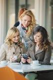 Grupo de las mujeres sonrientes en la cafetería Imágenes de archivo libres de regalías