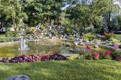 Grupo de las pequeñas fuentes de agua que fluyen en jardín de rocalla delantero de la belleza Fotos de archivo