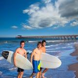 Grupo de las personas que practica surf de los muchachos que sale de la playa Imagen de archivo libre de regalías
