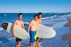 Grupo de las personas que practica surf de los muchachos que sale de la playa Imagenes de archivo
