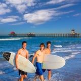 Grupo de las personas que practica surf de los muchachos que sale de la playa Foto de archivo