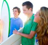 Grupo de las personas que practica surf del adolescente feliz en orilla de la playa Imagenes de archivo