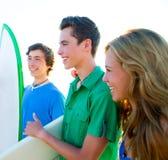 Grupo de las personas que practica surf del adolescente feliz en orilla de la playa Imagen de archivo libre de regalías