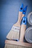 Grupo de latas das escovas de pintura na placa de madeira Imagens de Stock Royalty Free