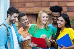 Grupo de latino e de estudantes afro-americanos que falam sobre trabalhos de casa imagem de stock