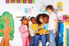 Grupo de libro de lectura de los niños con el profesor en cuarto de niños fotos de archivo