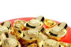 Grupo de lingotes dourados no isolado vermelho da bandeja no fundo branco C foto de stock