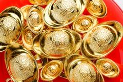 Grupo de lingotes de oro en la bandeja roja en el fondo rojo Nuevo chino Foto de archivo