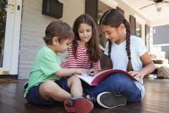 Grupo de livros de leitura de Sit On Porch Of House das crianças junto fotos de stock