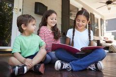 Grupo de livros de leitura de Sit On Porch Of House das crianças junto foto de stock