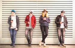 Grupo de los amigos que usa smartphone contra la pared en la rotura del patio trasero de la Universidad - gente joven enviciada p imagen de archivo