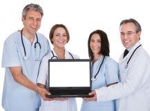 Grupo de los doctores With A Laptop imagenes de archivo