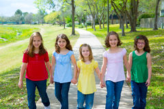 Grupo de los niños de muchachas y de amigos de las hermanas que caminan en parque Imágenes de archivo libres de regalías