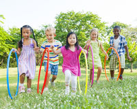 Grupo de los niños Hula Hooping en el parque Fotos de archivo