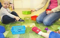 Grupo de los niños que hace artes y artes en guardería Niños que pasan tiempo en centro de cuidado de día con el gran interés imágenes de archivo libres de regalías