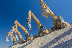 Grupo de máquinas escavadoras no monte do cascalho Fotografia de Stock Royalty Free
