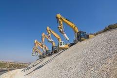 Grupo de máquinas escavadoras no monte do cascalho Imagens de Stock Royalty Free