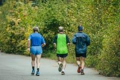 Grupo de más viejos hombres que corren abajo del camino en el parque Imagen de archivo libre de regalías