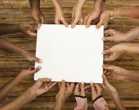 Grupo de mãos da diversidade que guardam o papel vazio imagem de stock