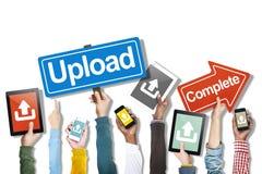 Grupo de mãos que guardam dispositivos de Digitas com conceito da transferência de arquivo pela rede imagem de stock