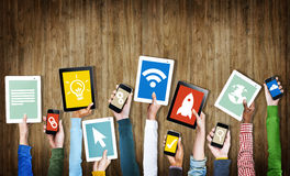 Grupo de mãos que guardam dispositivos de Digitas com símbolos Imagens de Stock Royalty Free