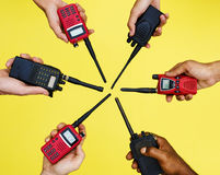 Grupo de mãos que guardam rádios em dois sentidos portáteis com fundo amarelo Fotos de Stock