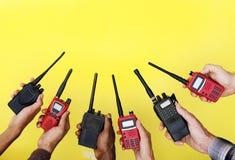 Grupo de mãos que guardam rádios em dois sentidos portáteis com fundo amarelo Fotografia de Stock Royalty Free