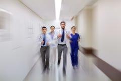 Grupo de médicos que caminan a lo largo de hospital Imágenes de archivo libres de regalías