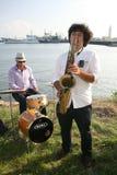 Grupo de músicos da rua no fundo do Golfo da Finlândia no porto civil de Kronstadt Fotos de Stock Royalty Free